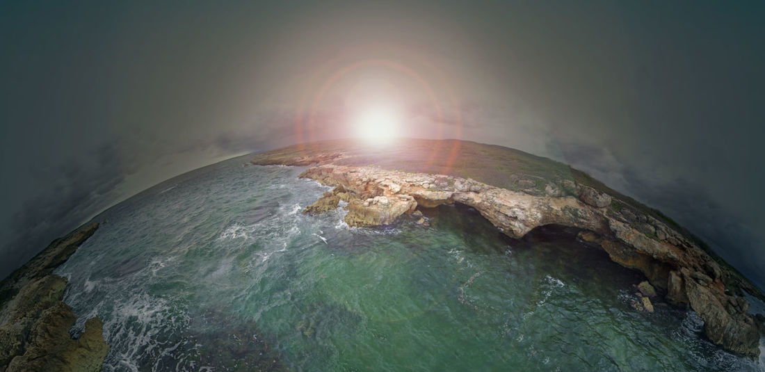A highly stylised image of two sea coasts in Puerto Rico. The sun is rising over the top edge of the earth. Colors and edits make the image surreal. Beauty In Nature Cliff Earth Geology Globe Majestic Natural Landmark No People Non-urban Scene ObsessiveEdits Outerspace Physical Geography Rock Formation Sea Seascape Sun Sunrise Sunset Surrealism Tranquil Scene Tranquility Water Wave