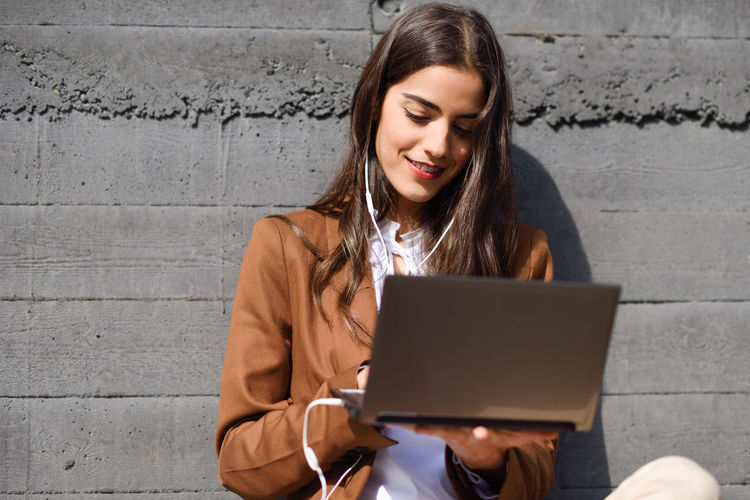 Young businesswoman using laptop while sitting against wall