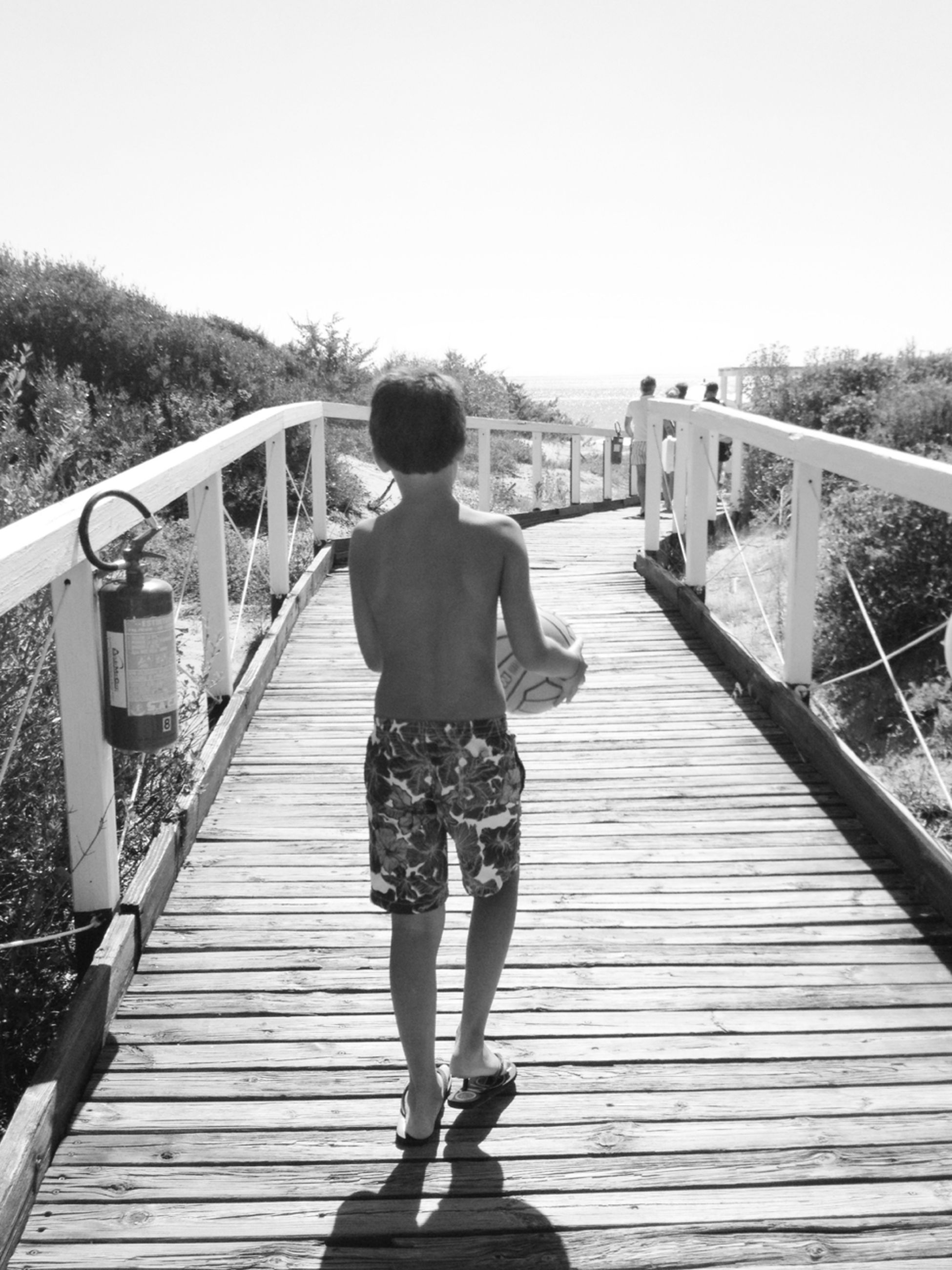 railing, full length, lifestyles, footbridge, rear view, leisure activity, the way forward, bridge - man made structure, connection, casual clothing, boardwalk, wood - material, clear sky, standing, walking, bridge, water, pier