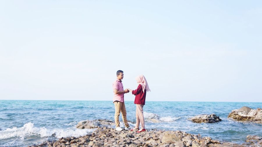 Couple standing on rock against clear sky