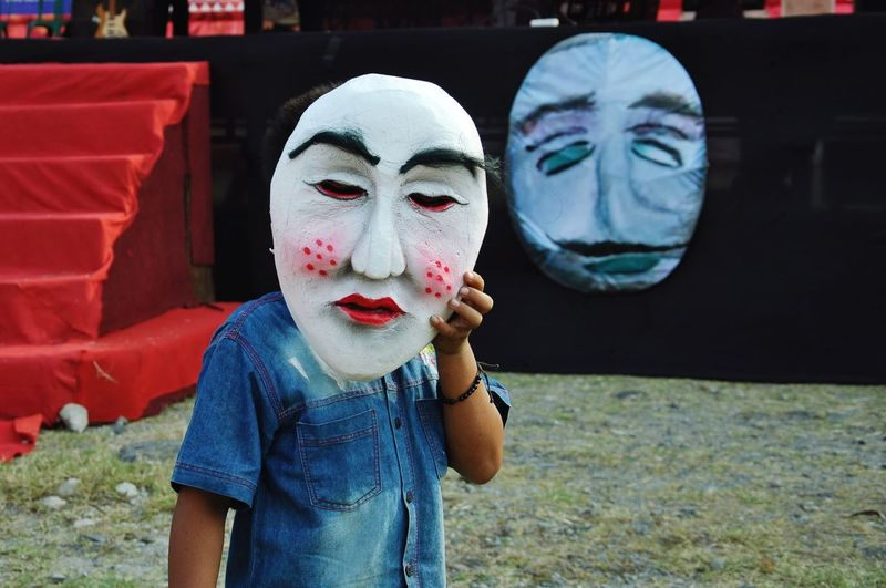 Teenage boy holding big mask while standing against stage