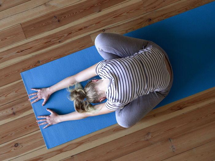 High angle view of woman lying on hardwood floor at home