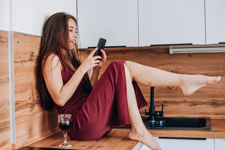 Young woman using mobile phone at home