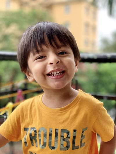 Portrait of smiling boy standing against railing