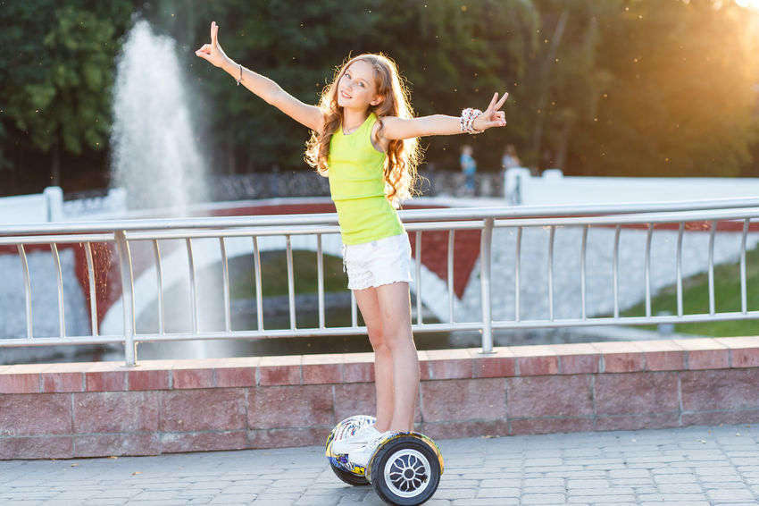 Happy girls riding on hover boards or gyroscooters outdoors at sunset in summer. Active life concept Hair Happiness Hover Board Casual Clothing Day Girl Gyroboard Hoverboard Leisure Activity Lifestyles Long Hair Motion One Person Outdoors Real People Smiling Street Sunset