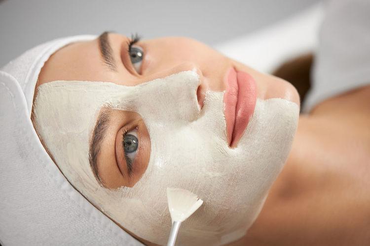 Close-up portrait of woman applying facial mask at spa