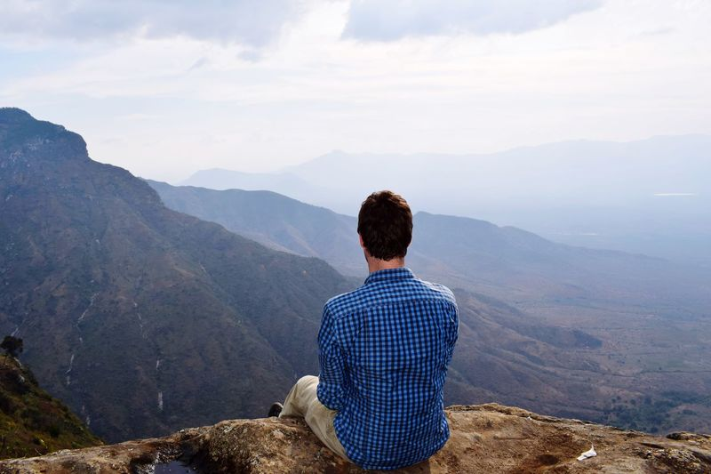 Rear view of man looking at landscape while sitting on mountain against sky