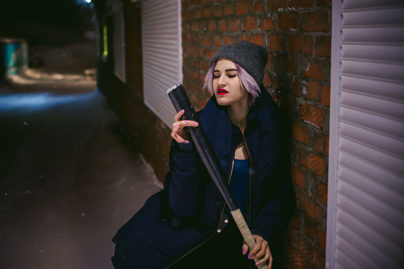 Young woman with baseball bat standing outdoors at night