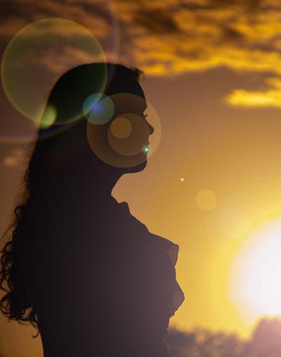 Portrait of silhouette woman against orange sky