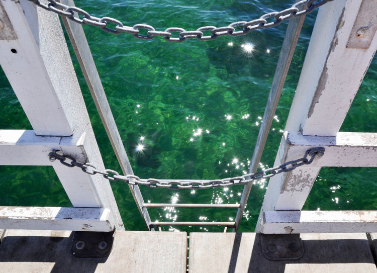 View of Busselton Jetty ladder with rail and chain descending into the glistening Indian Ocean in Western Australia. Abstract Busselton Chain Chainlink Closeup Day Descending Glistening Green High Angle View Indian Ocean Jetty Ladder Metal Nature Outdoors Railing Rungs Sea Sunlight Turquoise View From Above Water Western Australia Wooden
