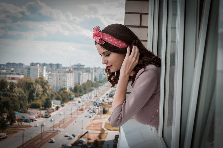 Woman peeking from window in city