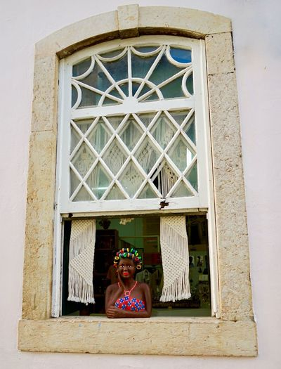 Portrait of woman standing against window of building