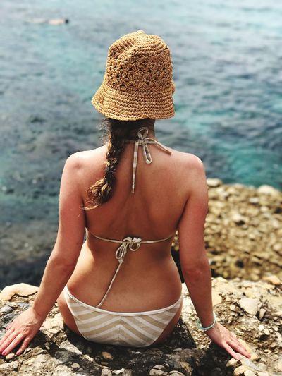 Rear view of woman in bikini sitting on rocky shore