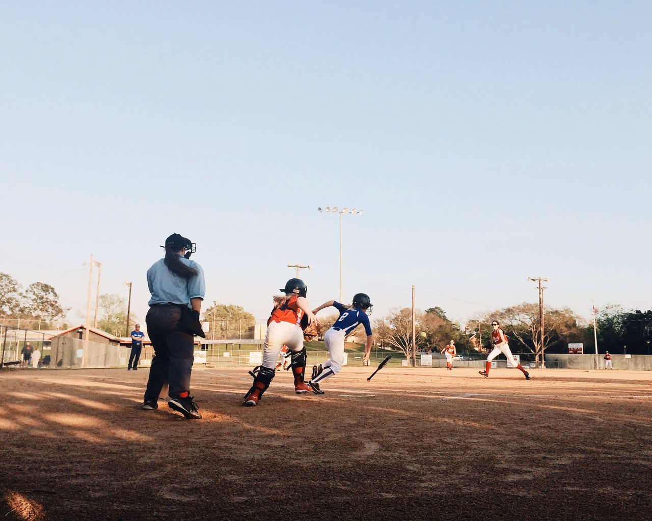 Children playing baseball against clear sky