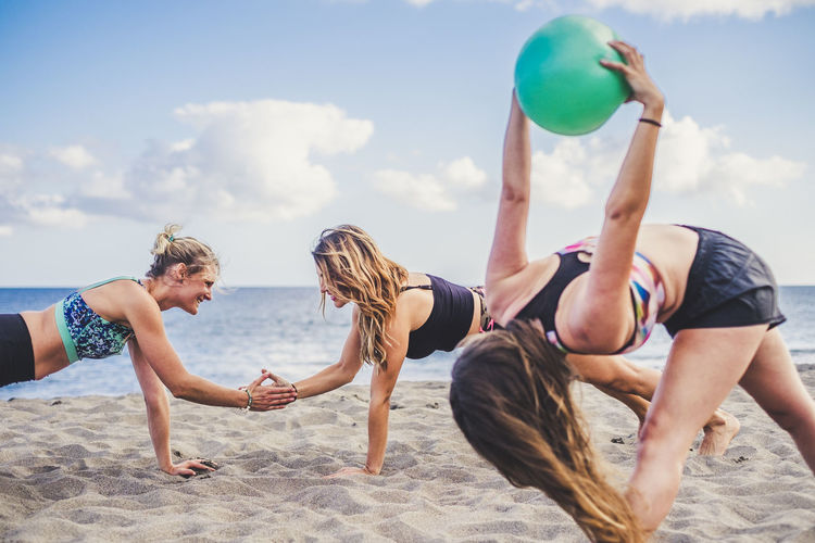 Women playing at beach against sky