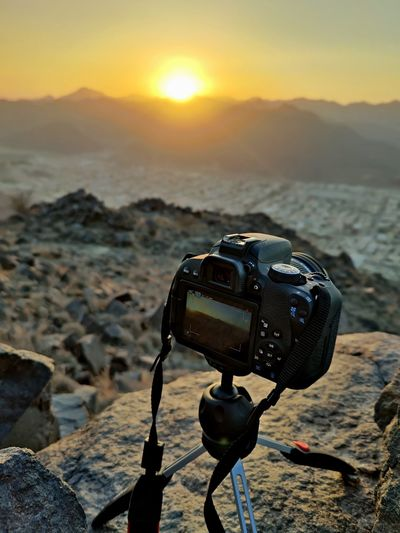 Close-up of camera on beach against sunset sky