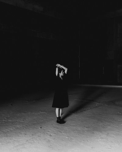 Full length of woman standing on ground at night
