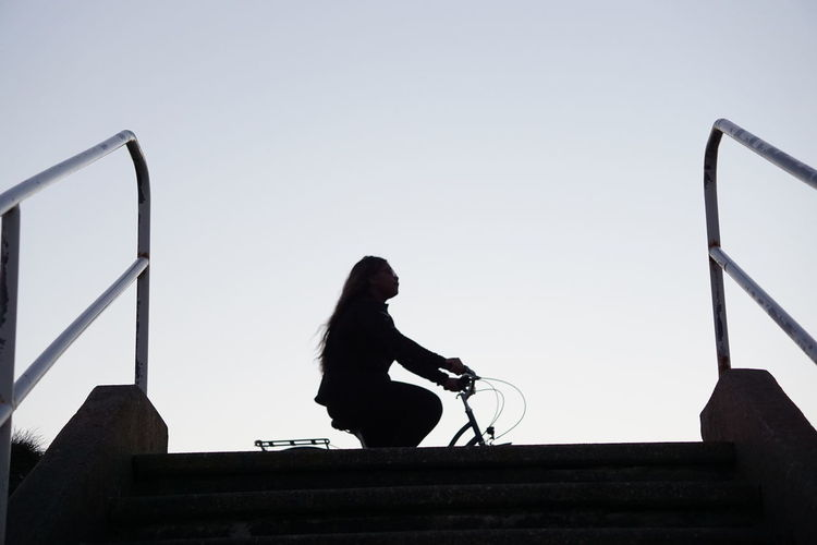 Low angle view of man sitting on railing against sky
