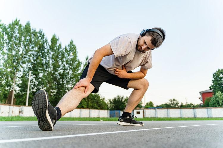 Full length of young man skateboarding on road against sky