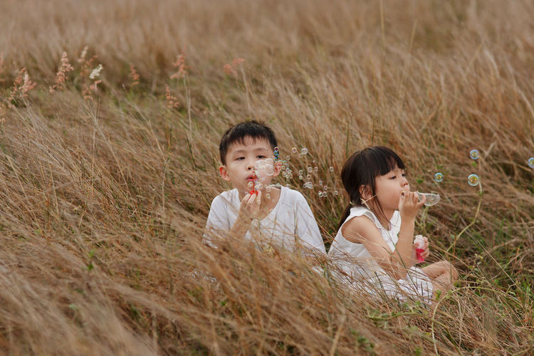 Siblings blowing bubbles while sitting on field