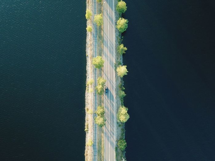 Aerial view of car on bridge by sea