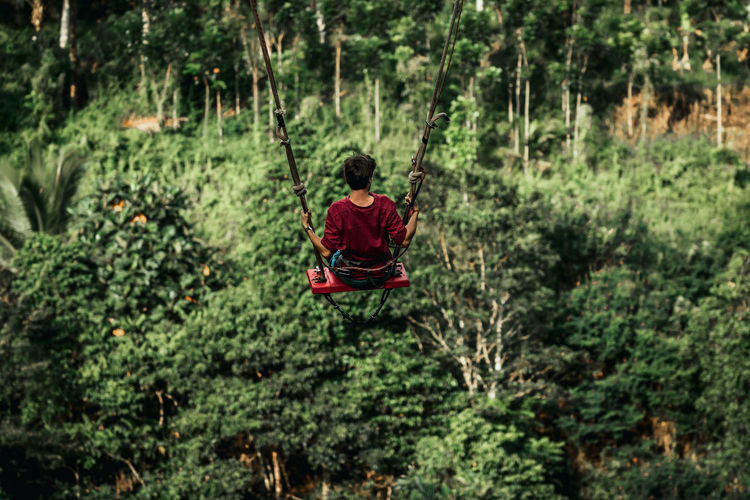 Man holding rope in forest