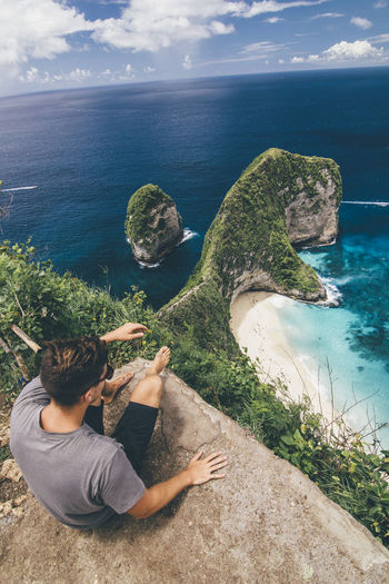 High angle view of man sitting on cliff against sea