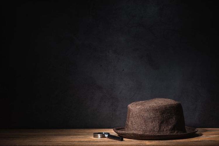 Hat and magnifying glass against black background on table