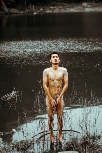 Naked Man Standing At Lake