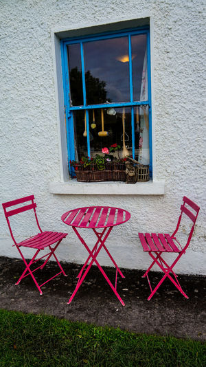 Pink color table and chair outside a kitchen Architecture Blue Building Exterior Chair Day Flower Kitchen Utensils No People Outdoors Pink Color Table Window