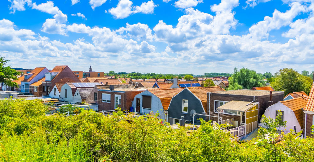 Panoramic view of houses and buildings against sky