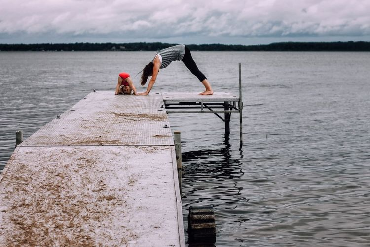 Yoga on a dock. Water Pier Jetty Cloud - Sky Sea Day Outdoors Two People Sky Diving Platform Men Young Men Young Adult Full Length Nature Real People Scenics Young Women Beauty In Nature Adult