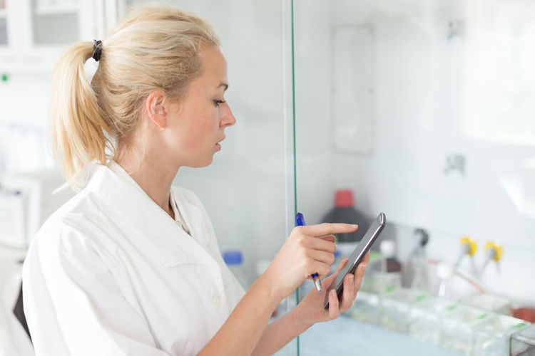 Side view of woman using mobile phone at laboratory