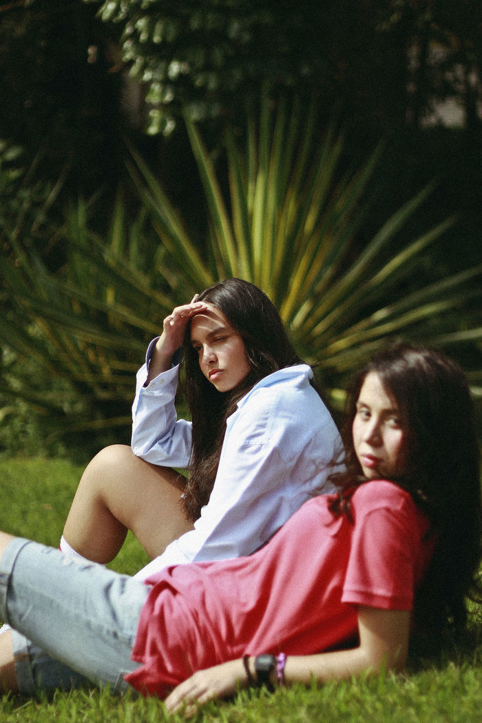 Friends resting on field against trees