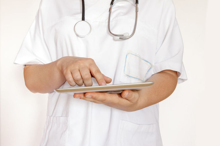 Midsection of doctor using digital tablet against white background