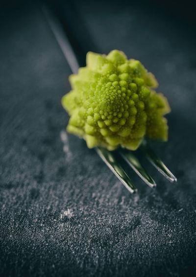 Romanesco cauliflower on fork at table