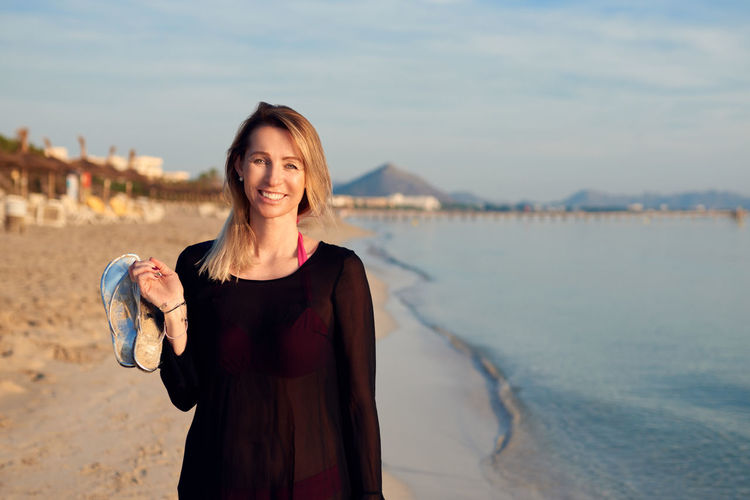 Portrait of smiling woman standing at beach