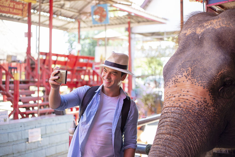 Man taking selfie while standing by elephant