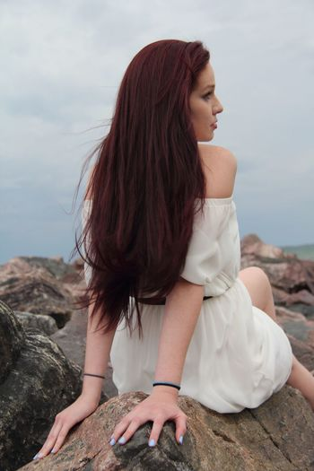 Rear View Of Young Woman With Long Hair Sitting On Rock Against Sky