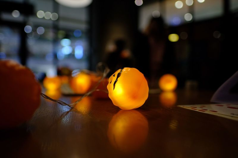 Close-up of illuminated lighting equipment on table at home during halloween