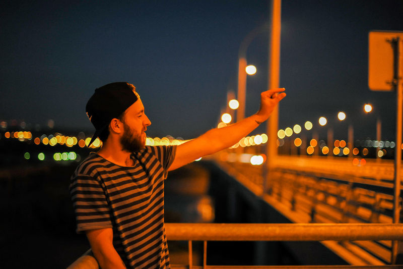 Young man gesturing on bridge at night