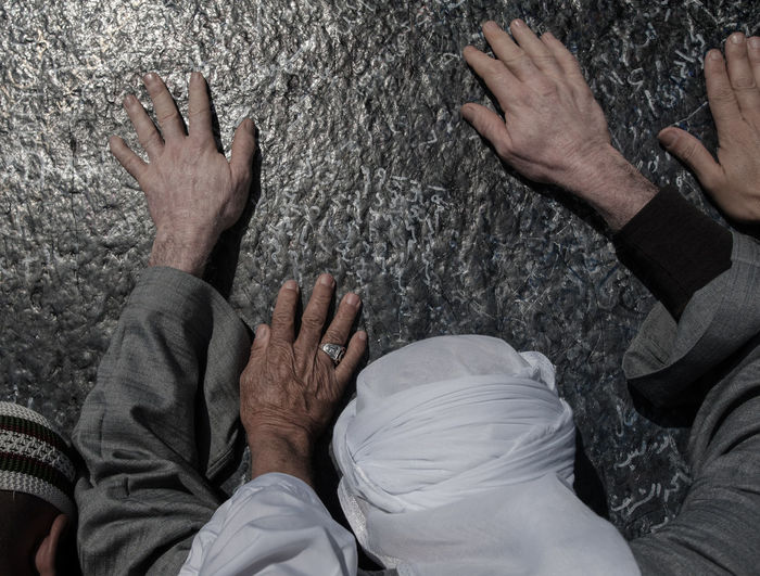 Close-up of men praying at mount arafat