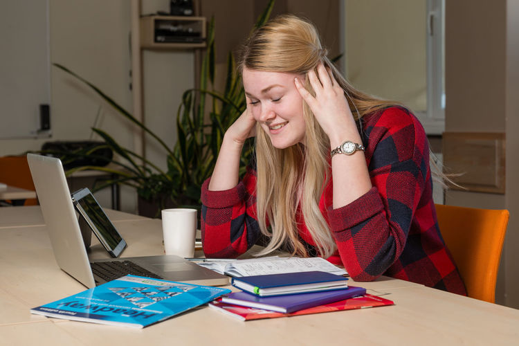 Smiling Young Woman With Eyes Closed Sitting By Laptop On Desk