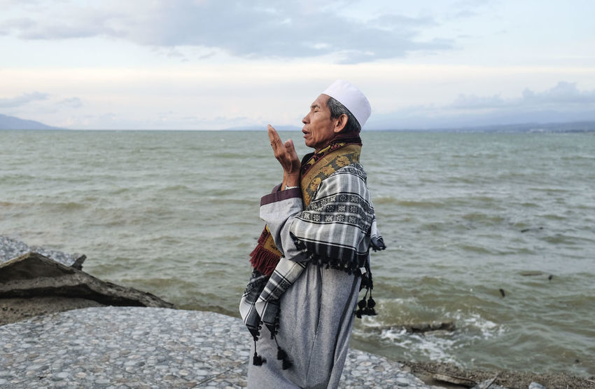 Muslim man recite a doa during mass prayer for earthquake and tsunami victim at Talise Beach Water Sea Sky Standing Casual Clothing Real People Side View Beach Scenics - Nature Young Adult Cloud - Sky Adult Beauty In Nature Horizon Over Water Wireless Technology Outdoors Muslim Recites And Pray Islamic INDONESIA Earthquake Effects Autumn Mood EyeEmNewHere