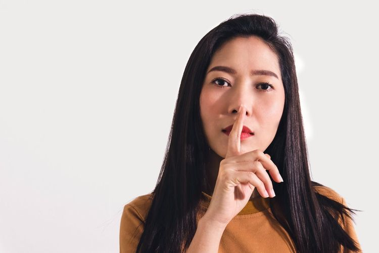 Portrait of woman with finger on lips against white background