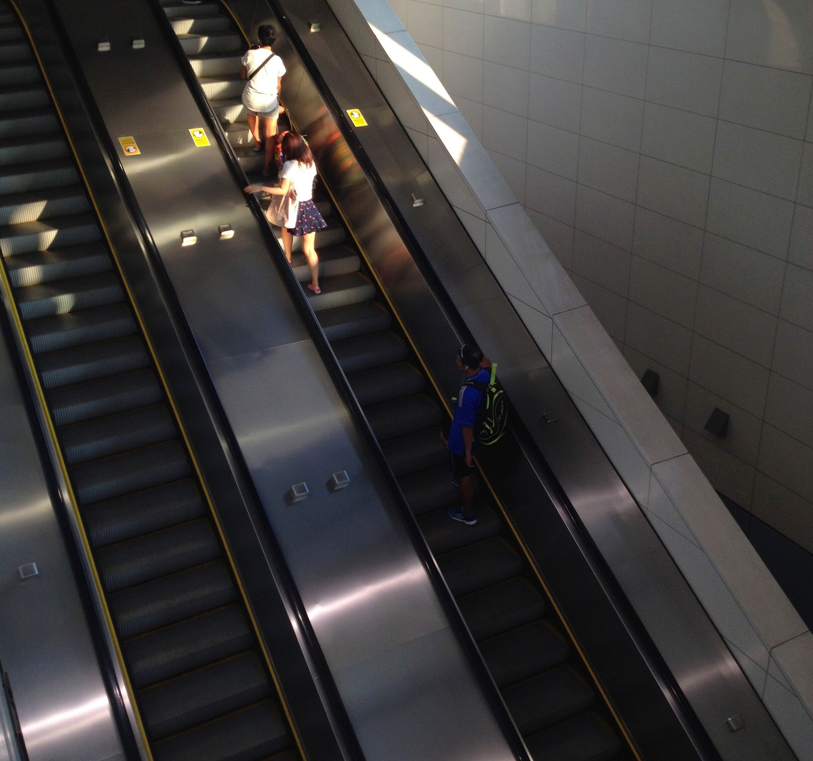 indoors, steps, steps and staircases, staircase, escalator, high angle view, lifestyles, men, railing, person, walking, leisure activity, moving down, full length, modern, the way forward, built structure, moving up