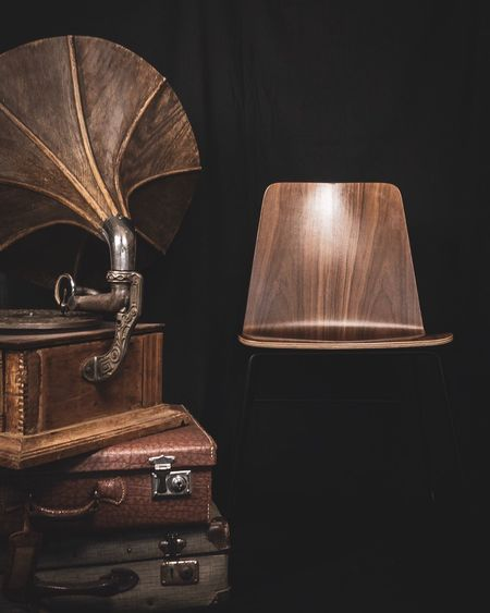 Wooden Chair With Gramophone And Suitcase On Black Background
