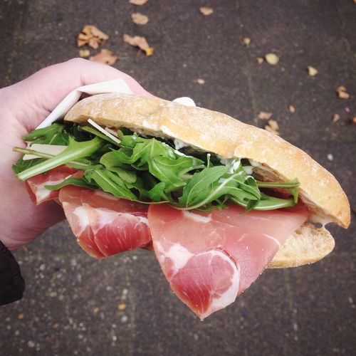 Cropped Image Of Hand Holding Sandwich At Street