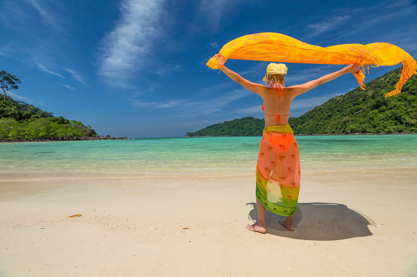 Back of happy and fashionable tourist woman with colorful sarong in turquoise water of Maya Bay famous lagoon of The Beach movie, Phi Phi Leh, Andaman Sea in Thailand Fashionable and happy tourist with sarong and pink wide-brimmed hat making a selfie on tropical famous beach of Nai Harn Beach, Rawai, Phuket, Thailand. Happy tourist enjoys panorama from Sail Rock View Point of kor 8 of Similan Islands National Park, Phang Nga, Thailand, one of the tourist attraction of the Andaman Sea. Happy woman with bikini and shorts, jumping in the air on Ya Nui Beach, a little cove divided by a rocky cape, Phuket, Thailand, Asia. Happy Koh Rok Islands Nui Beach Phang Nga Bay Phuket Thailand Tanning ☀ Thailand Vacations Woman Beach Beauty In Nature Blue Cloud - Sky Day Girl Horizon Over Water Koh Rok Nature One Person Outdoors People Phang Nga Rawai Real People Sand Scenics Sea Seascape Sky Sunlight Surin Islands Travel Destinations Tree Vacations Water Women Young Adult