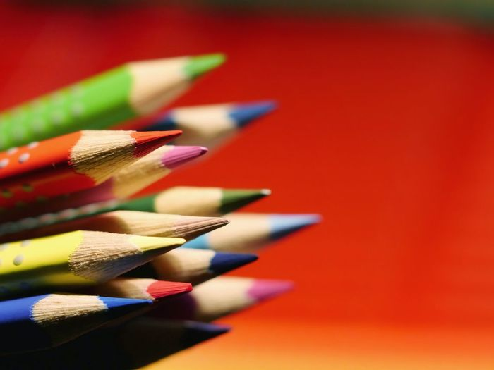 Close-Up Of Multi Colored Pencils Against Red Background
